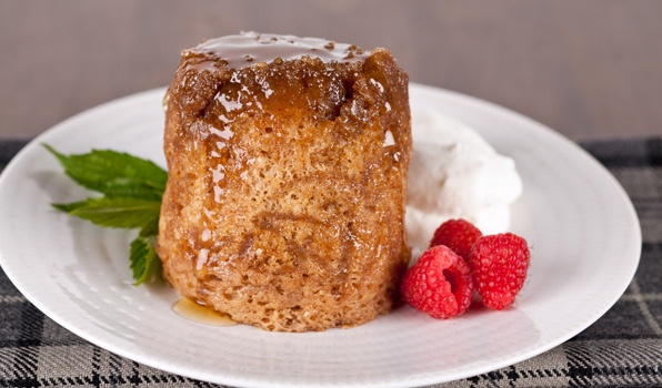 in the kitchen with stefano faita sticky apple pudding drizzled with maple syrup and served on a plate with a dollop of whipped cream and raspberries
