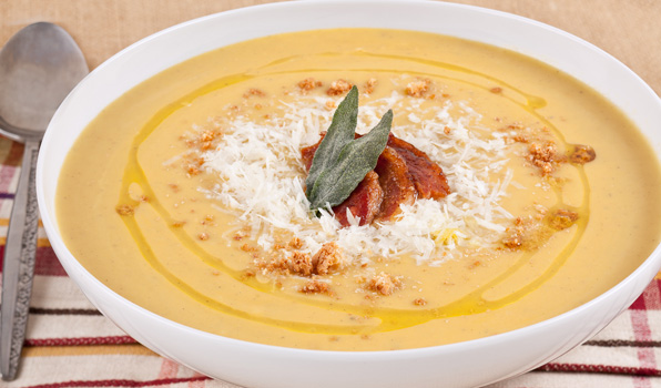 in the kitchen with stefano faita roasted butternut squash soup in a bowl, garnished with crushed amaretti cookies, pancetta, parmesan cheese, fried sage leaves and reserve sage oil
