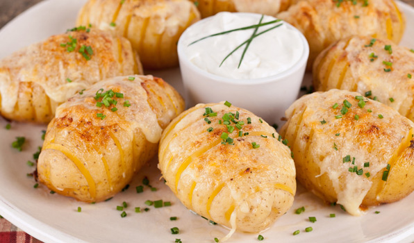 in the kitchen with stefano faita cheesy fan potatoes with chopped chives as garnish and sour cream for dipping