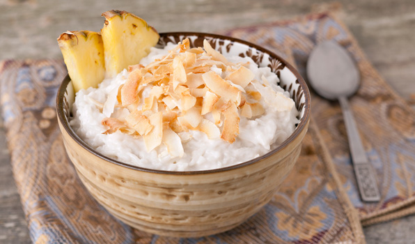 in the kitchen with stefano faita coconut rice pudding in a bowl garnished with coconut shavings and pineapple slice