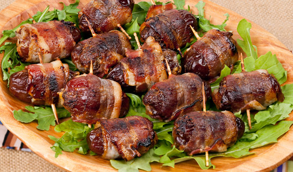 in the kitchen with stefano faita devils on horseback with arugula leaves on a wooden dish