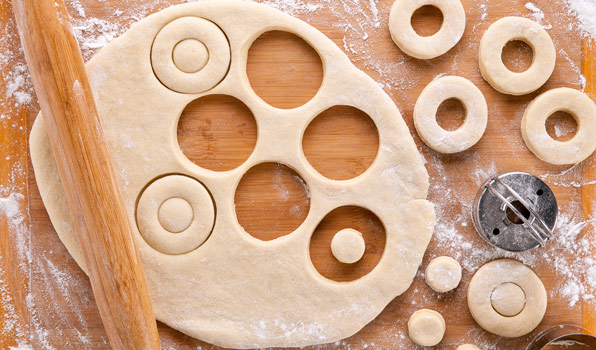 in the kitchen with stefano faita all purpose donut dough uncooked on a wooden board with portions cut out with a cookie cutter and rolling pin