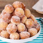 in the kitchen with stefano faita vanilla sugar donut holes piled on a white dish with vanilla beans on the side
