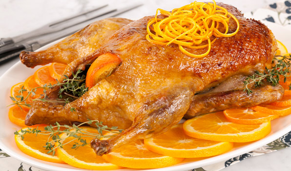 in the kitchen with stefano faita stefano's duck a l'orange on a platter garnished with orange slices, blanched orange zest and thyme sprigs and served with orange sauce