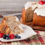 in the kitchen with stefano faita giant cinammon bun slice with cream cheese icing on a plate with mixed berries