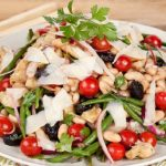 In the Kitchen with Stefano Faita Artichoke and Green Bean Salad served on a plate with wooden spoons