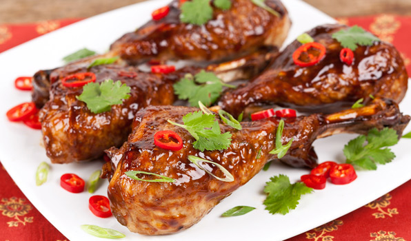 in the ktichen with stefano faita honey spiced turkey drumstick on a plate with sliced red finger chiles, chopped green onions and cilantro leaves as garnish