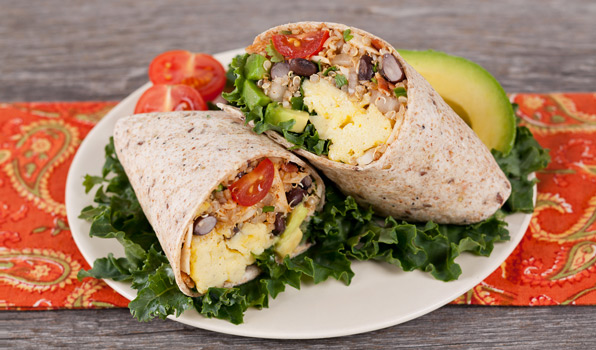 in the kitchen with stefano faita huevos rancheros burrito on a plate with a slice of avocado, cherry tomatoes and kale as decoration