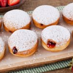 in the kitchen with stefano faita jelly donuts served on a wooden board with strawberries on the side