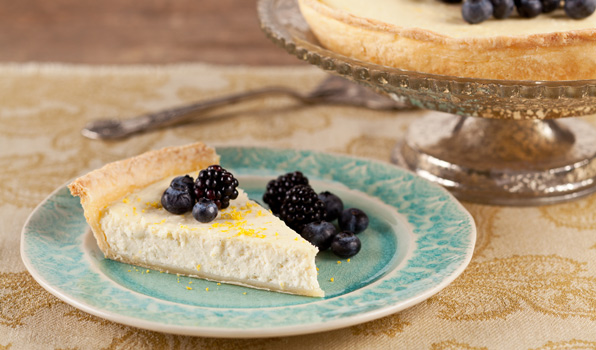 in the kitchen with stefano faita lemony ricotta pie slice on a plate with lemon zest, blueberries and raspberries on top