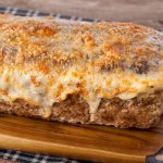 in the kitchen with stefano faita cheesy 3 meat meatloaf served on wooden cutting board