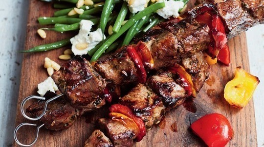 gino's italian escape grilled lamb skewers with a green bean and goat's cheese salad served on wooden cutting board