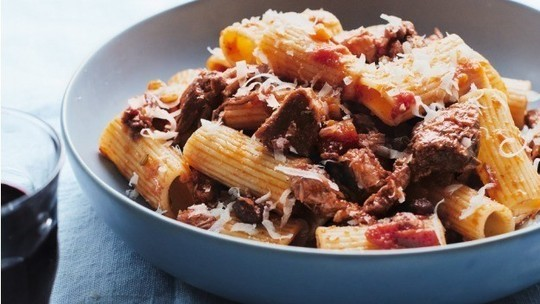 gino's italian escape rigatoni with wild boar ragu served in bowl and topped with shredded parmesan cheese