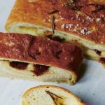 gino's italian escape bread stuffed with salami, cheese and vegetables sliced and served