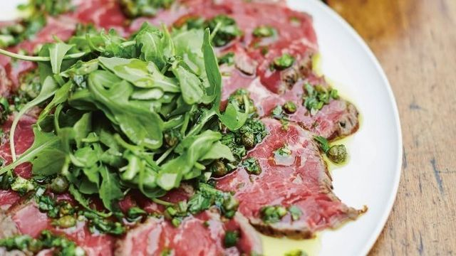 gino's italian escape carpaccio of beef with gremolata placed on large platter and dressed with rocket leaves and extra virgin olive oil
