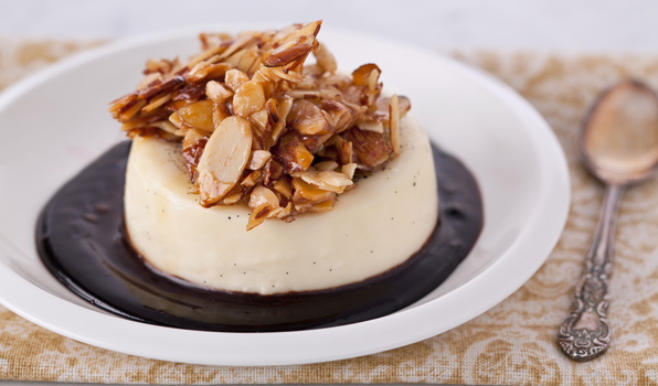 in the kitchen with stefano faita almond panna cotta with chocolate sauce topped with a cluster of candied almonds