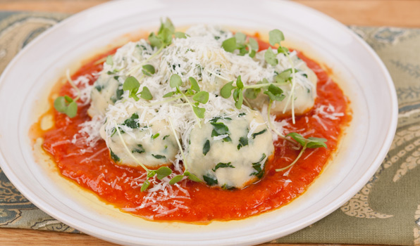 in the kitchen with stefano faita ricotta and spinach gnudi with roasted tomato sauce served on a white plate