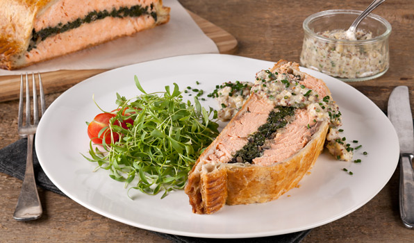 in the kitchen with stefano faita stefano's salmon wellington served on a dish with leek and mustard cream sauce and garnished with micro greens