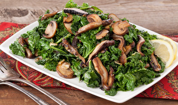 in the kitchen with stefano faita lemony greens with mushrooms served on a plate with a slice of lemon