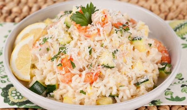 in the kitchen with stefano faita shrimp and zucchini risotto served with grated parmesan cheese and garnished with lemons and parsley