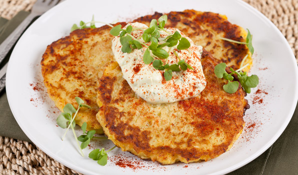 in the kitchen with stefano faita spaghetti squash latkes served on a plate with a dollop of curry yogurt dip on top