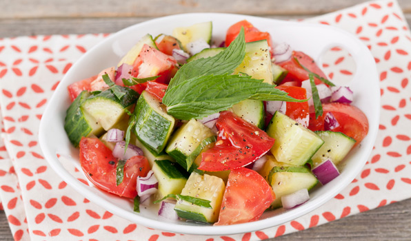 in the kitchen with stefano faita fresh tomato and cucumber salad served in a white bowl with mint leaf as garnish