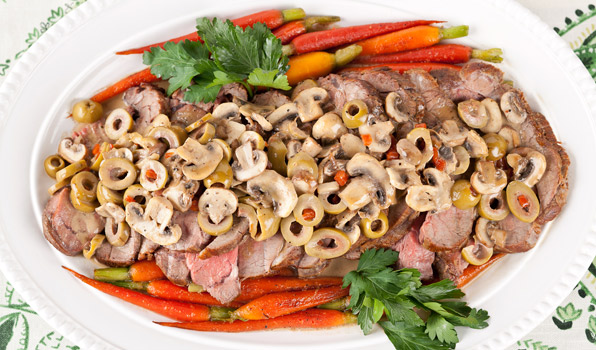 in the kitchen with stefano faita veal roast with mushrooms and olives served on a platter with honey glazed baby carrots