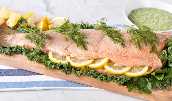 in the kitchen with stefano faita oven poached salmon with green goddess dressing on a cutting board garnished with kale leaves, lemon slices, parsley and fennel fronds